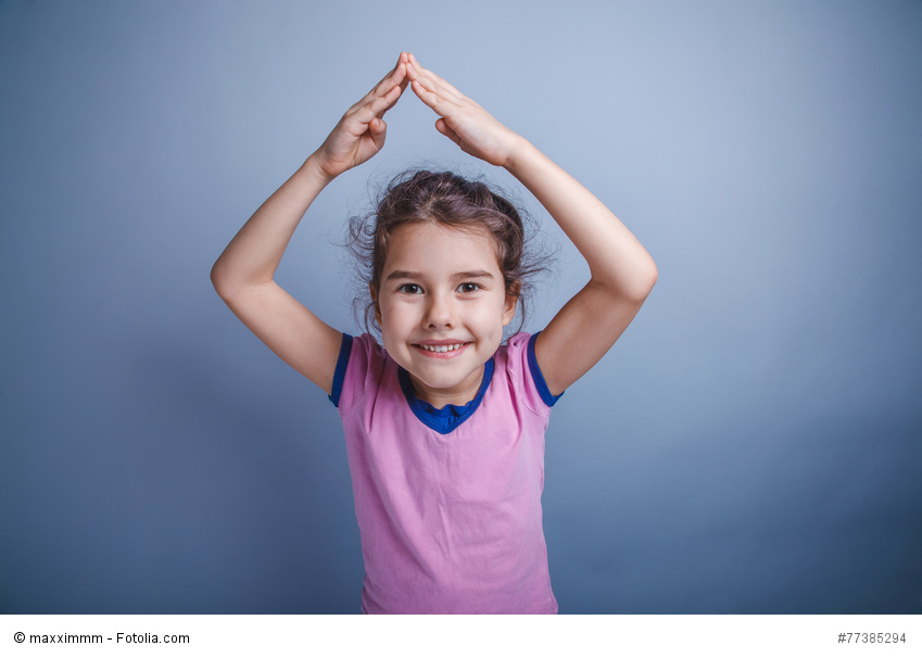 baby girl of European appearance 6 years hands above his head on