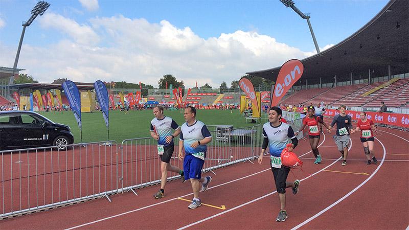 E.ON Kassel Marathon 2016, Läufer der IMMOVATION AG beim Zieleinlauf im Auestadion
